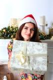 拿着有圣诞节礼物的美丽的微笑的女孩一个箱子 库存图片