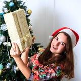 拿着有圣诞节礼物的美丽的微笑的女孩一个箱子 免版税图库摄影