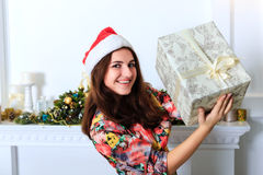 拿着有圣诞节礼物的美丽的微笑的女孩一个箱子 免版税库存图片