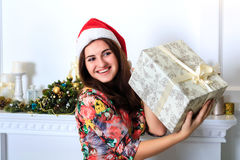 拿着有圣诞节礼物的美丽的愉快的女孩一个箱子 库存图片