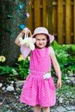 拿着有复活节兔子的小女孩一个钱包 免版税库存图片