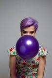 拿着有她的嘴的,神色的紫罗兰色短发女孩一个气球 免版税库存图片