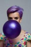 拿着有她的嘴的,神色的紫罗兰色短发妇女一个气球 免版税库存图片