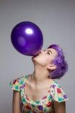 拿着有她的嘴的,神色的紫罗兰色短发妇女一个气球 免版税图库摄影