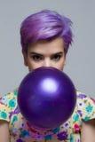拿着有她的嘴的紫罗兰色短发妇女一个气球 库存照片