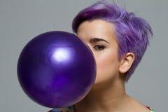 拿着有她的紫罗兰色短发妇女特写镜头一个气球 免版税库存照片