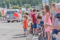 拿着有孩子的红色气球和父母的年轻男孩观看游行 免版税库存照片