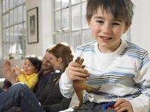 拿着有家庭的男孩动物玩具微笑在背景中 免版税库存图片
