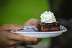 拿着有巧克力蛋糕的阿芒迪娜的手板材 免版税库存照片