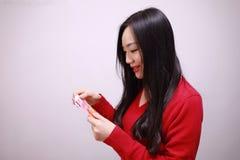拿着有幸运的金钱的中国女孩红色小包妇女举行 免版税库存照片