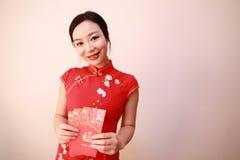 拿着有幸运的金钱的传统礼服cheongsam的中国女孩红色小包妇女举行 免版税库存图片