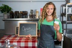 拿着有开放标志和一次性咖啡杯的男职工一个委员会 免版税库存图片