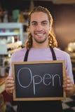 拿着有开放标志的微笑的侍者画象黑板 免版税库存照片
