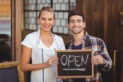 拿着有开放标志的微笑的女服务员和人黑板 免版税库存图片