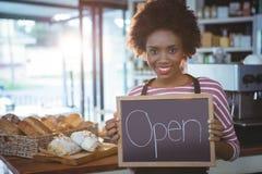 拿着有开放标志的微笑的女服务员黑板 库存照片