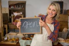 拿着有开放标志的微笑的女职工画象黑板在柜台 免版税库存图片
