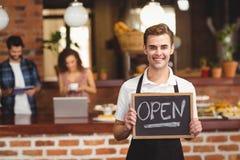 拿着有开放标志的微笑的barista黑板 免版税图库摄影