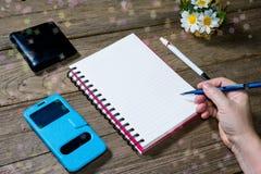 拿着有开放笔记本的人的手传动器型的铅笔 图库摄影