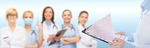 拿着有心电图的女性医生剪贴板 库存照片