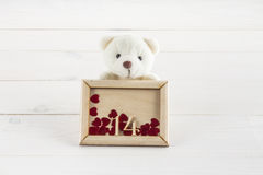 拿着有心脏的白色玩具熊板材 2月的14日概念 库存照片
