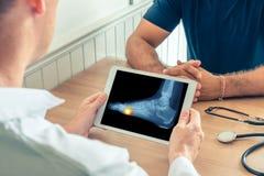 拿着有患者的脚X-射线的医生一种数字片剂  在脚下的痛苦 免版税库存照片