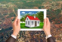 拿着有房子的图象的手片剂个人计算机的 免版税库存图片