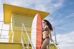拿着有拷贝空间的引诱的拉丁妇女画象冲浪板您的品牌的,当站立在救生员房子时 免版税库存照片