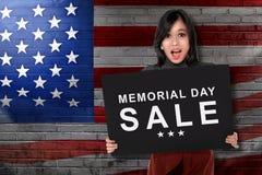 拿着有文本阵亡将士纪念日销售的年轻亚裔妇女委员会 免版税库存照片