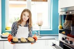 拿着有新近地被烘烤的小圆面包的主妇热的烧烤平底锅 库存图片