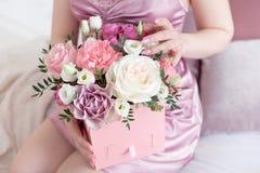 拿着有新鲜的罗斯和糖果的年轻作的妇女方形的桃红色花箱子 免版税库存照片
