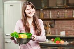 拿着有新鲜蔬菜的一个碗和微笑对照相机的妇女 在家烹调在厨房里的少妇 免版税图库摄影