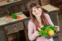 拿着有新鲜蔬菜的一个碗和微笑对照相机的妇女 在家烹调在厨房里的少妇 库存照片