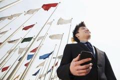 拿着有旗子的微笑的年轻商人一个电话在背景中 免版税库存图片