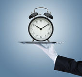 拿着有时钟的侍者银色盘子 免版税库存图片