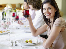 拿着有朋友的妇女葡萄酒杯在晚餐会 图库摄影