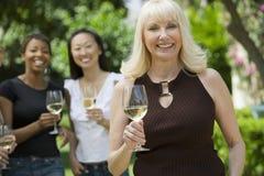 拿着有朋友的微笑的妇女葡萄酒杯在背景中 图库摄影