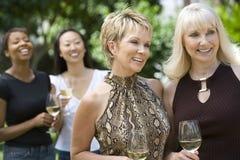 拿着有朋友的微笑的妇女葡萄酒杯在背景中 免版税库存照片