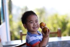 拿着有机桔子的年轻男孩 免版税库存照片