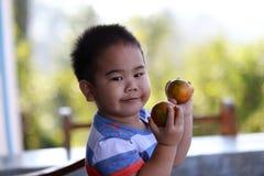 拿着有机桔子的年轻男孩 免版税图库摄影