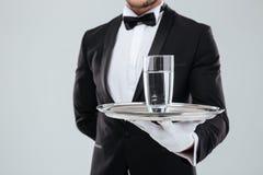 拿着有杯的手套的男管家银色盘子水 免版税图库摄影