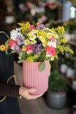 拿着有桃红色玫瑰、淡紫色翠菊、白色菊花和其他植物美好的插花的卖花人一个花瓶的 免版税库存图片