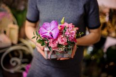 拿着有桃红色玫瑰和风信花的妇女一个箱子 库存图片