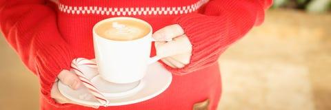 拿着有棒棒糖的女孩一个热奶咖啡杯子 基督的概念 库存图片