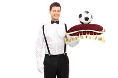 拿着有橄榄球的男管家一个红色枕头对此 免版税库存图片