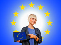 拿着有欧洲旗子的可爱的白肤金发的妇女片剂 图库摄影
