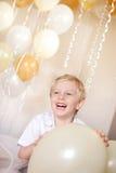 拿着有气球的一个年轻男孩一个气球在背景中。 库存照片