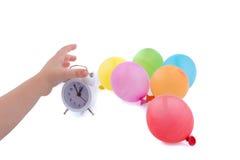 拿着有气球的手一个闹钟 免版税库存照片