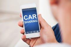 拿着有汽车分享的App的手巧妙的电话在屏幕上 图库摄影