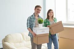 拿着有沙发的愉快的年轻夫妇移动的箱子在背景 免版税库存图片