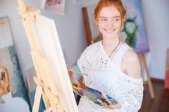 拿着有油漆的妇女画家调色板在艺术演播室 免版税库存照片